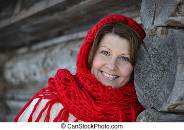 The Russian woman in shawl warms hands near an izba - The...