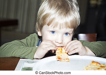 Boy child eating slice of pizza at restaurant