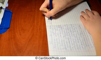 The boy writes in notebook homework on Russian language -...