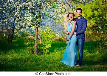 Young beautiful couple in love among apple trees