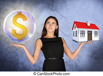 Woman holding dollar sign in bubble and house - Busineswoman...