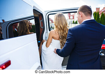 Newlyweds in a car - Bride and groom sit in a white car