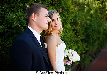 Embracing wedding couple - Bride and groom standing on the...