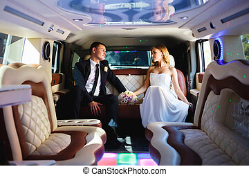 Newlyweds in a car - Happy bride and groom sitting in...