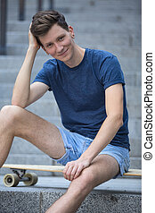 Guy with a long board - Cute guy with a sweet smile sitting...