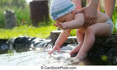 Baby playing in pond outdor in slowmotion Summer sunset time...