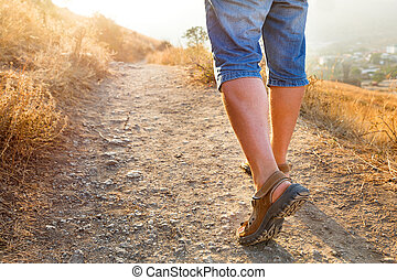 Active healthy travel - man in sports sandals climbs on the mountain. Closeup detail of male feet and stony path in sunset. Hiking in sunny day. Crimea, Russia.