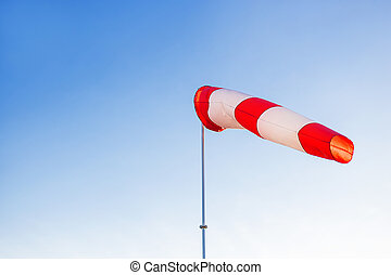 A red wind vane against a clear blue sky.