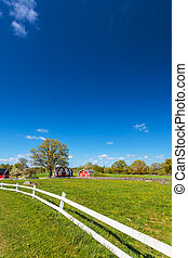 Old Swedish red wooden farm buildings with white fence