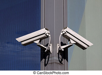 Security cameras - Two security cameras hanging on the...