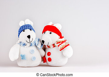 Pair of cute plush rabbits in warm clothes. Sweet couple of toys in scarfs and caps. Christmas background with empty space for text.