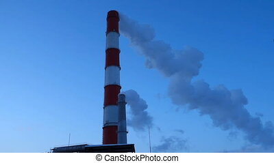 Two Smoking chimneys CHP at dusk. White smoke coming out of...
