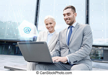 smiling businesspeople with laptop sending e-mail -...