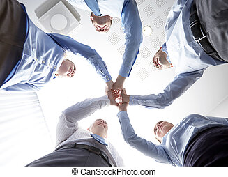 smiling group of businesspeople standing in circle -...