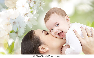 happy mother kissing her baby over cherry blossom - family,...