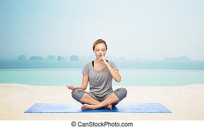 woman making yoga meditation in lotus pose on mat - fitness,...