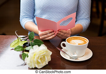 close up of woman reading greeting card and coffee -...
