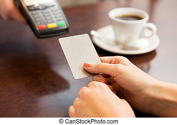 close up of hands with credit card reader at cafe - people,...