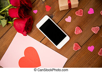 close up of smartphone, gift, red roses and hearts -...