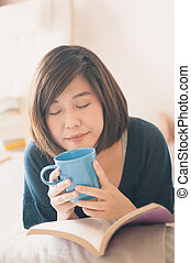 joven, asiático, mujer, lectura, libro, y, bebida, coffee.,