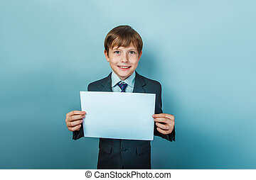 boy in a suit holding a blank sign