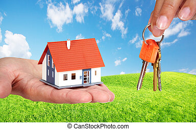 Small house and keys. - Woman hands with small house and...
