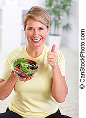 Elderly woman eating salad. Diet and nutrition concept...