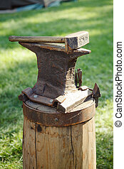 Worn iron anvil and hammer outdoors