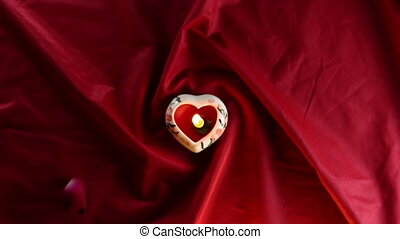 Candlelight with Sprinkle red roses petals on red fabric