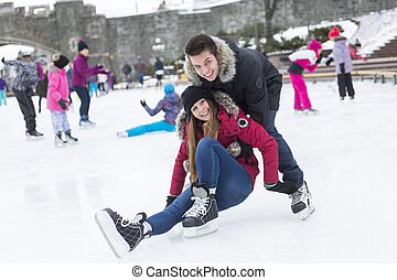 Ice skating couple having winter fun on ice skates Quebec,...