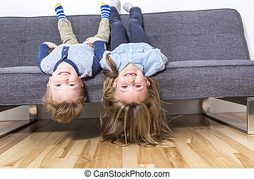 two nice child boy and girl on sofa - two nice beautiful...