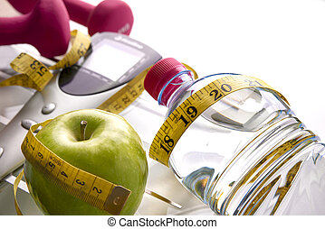 Scale with dumbbells bottle apple and tape measure elevated...