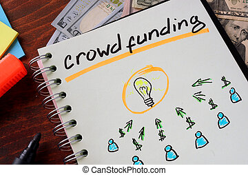 crowd funding - Notebook with crowd funding sign on a table....
