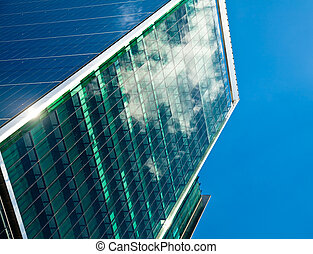Office building facade - Sky and clouds reflected in a...