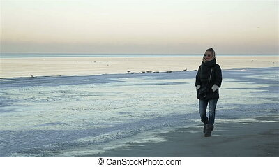 Lone sad beautiful girl walking along the shore of the frozen sea on a cold day