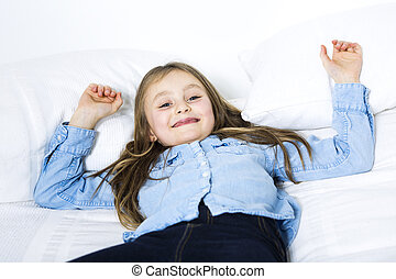 Adorable little girl looking at the camera on bed