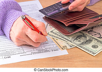 Filling out tax forms - A woman in a lavender sweater fills...