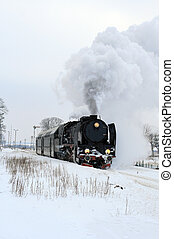 Old retro steam train starting from the station during...