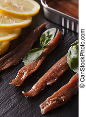 Anchovy fillets and lemon macro on a slate board. vertical -...
