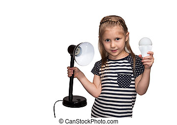 Little girl with lamp and luminaire - Girl in a striped...