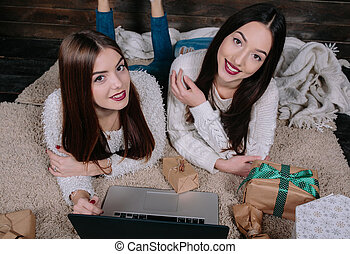 Two beautiful girls lie on the floor with a laptop, between...
