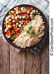 Couscous with vegetables and herbs vertical top view -...