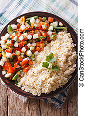 Couscous with vegetables and herbs closeup vertical top view...
