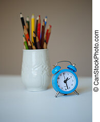 Little blue alarm clock and a glass with colored pencils on...