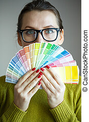 Woman in a glasses looking to a color palette - Woman in a...