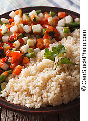 couscous with vegetable salad on a plate macro vertical -...