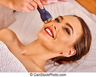 Young woman receiving electric facial massage - Portrait of...