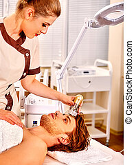 Young man receiving electric facial massage - Close up of...