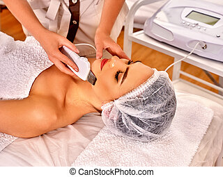Man receiving electric facial peeling massage - Woman...