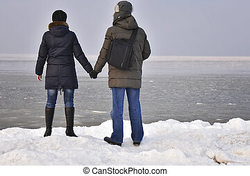 man and woman on the beach in the winter
